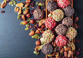 Homemade candy with chocolate, nuts and dried berries on a black table. Copy space.