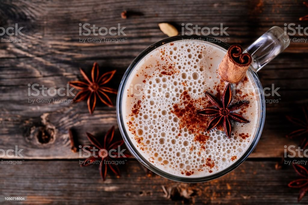 Homemade Chai Tea Latte with anise and cinnamon stick in glass mug. Top view stock photo