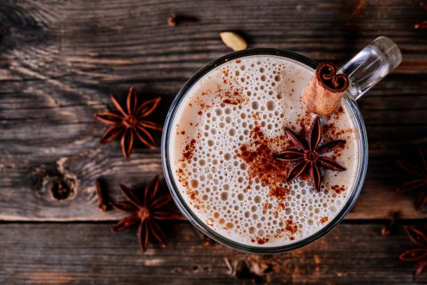 Homemade Chai Tea Latte with anise and cinnamon stick in glass mug. Top view Homemade Chai Tea Latte with anise and cinnamon stick in glass mug on wooden rustic background. Top view clove spice stock pictures, royalty-free photos & images