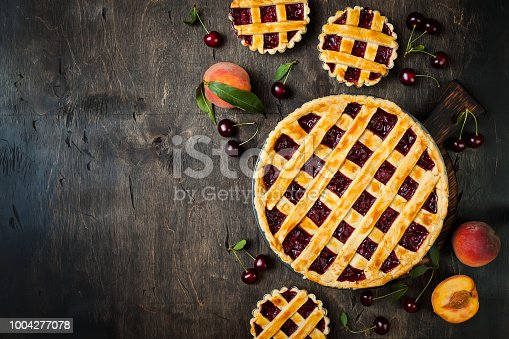 istock Homemade cherry pie on rustic wooden background 1004277078