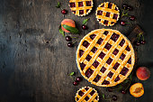 Homemade cherry pie on rustic background with cherries and peaches