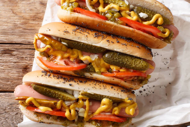 homemade chicago style hot dogs with mustard, tomatoes, pickled cucumbers, onions and relish close-up. horizontal top view - hot dog stock pictures, royalty-free photos & images