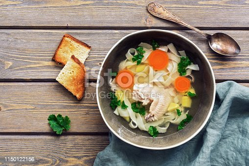 Homemade chicken noodle soup on a wooden rustic plank table. Top view, copy space