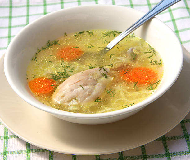 Homemade chicken soup in white bowl stock photo