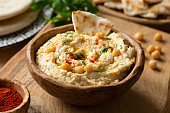 Homemade chickpea hummus bowl with pita chips and paprika