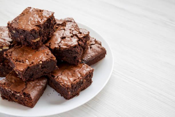 hemlagad choklad brownies på en vit tallrik på en vit trä bakgrund, sidovy. kopiera utrymme. - brownie bildbanksfoton och bilder
