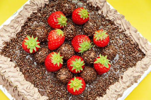 """Homemade chocolate cake covered with chocolate sprinkles and fresh strawberries. Known in Brazil as """"Bolo de Brigadeiro"""". Isolated on yellow background. Top view. Horizontal shot"""