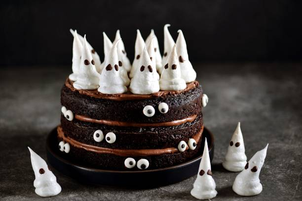 Homemade Chocolate Cake with Chocolate cream and Meringue Ghost and Eyes for Halloween Party. stock photo