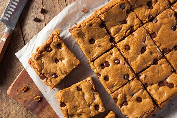 homemade chocolate chip blondies - kauwgomachtig stockfoto's en -beelden