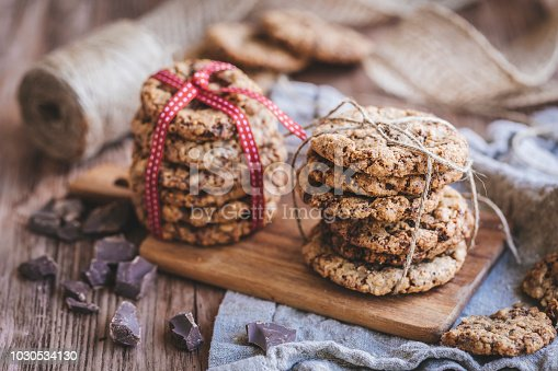 Homemade chocolate chip cookies. The cookies are  tied together with ribbons, one of the piles with a red and white ribbon. The cookies are on a wooden chopping board and there are pieces of chocolate next to it.