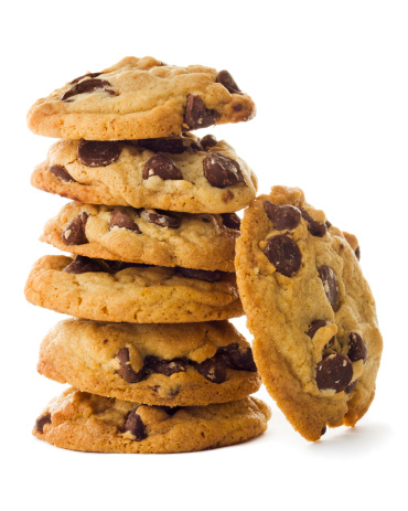 Fresh, homemade chocolate chip cookies stacked in vertical tower of six morsels. One piece leans against the pile. The baked, gourmet dark chocolate treat is a favorite dessert or after-school snack with milk. The sweet food indulgence contributes to overeating fats and sugars, an unhealthy diet. Isolated on white background.
