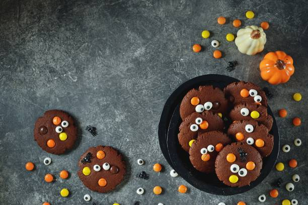 Homemade Chocolate Chip Cookies whith spooky candy eyes for Halloween Party. Halloween background. stock photo