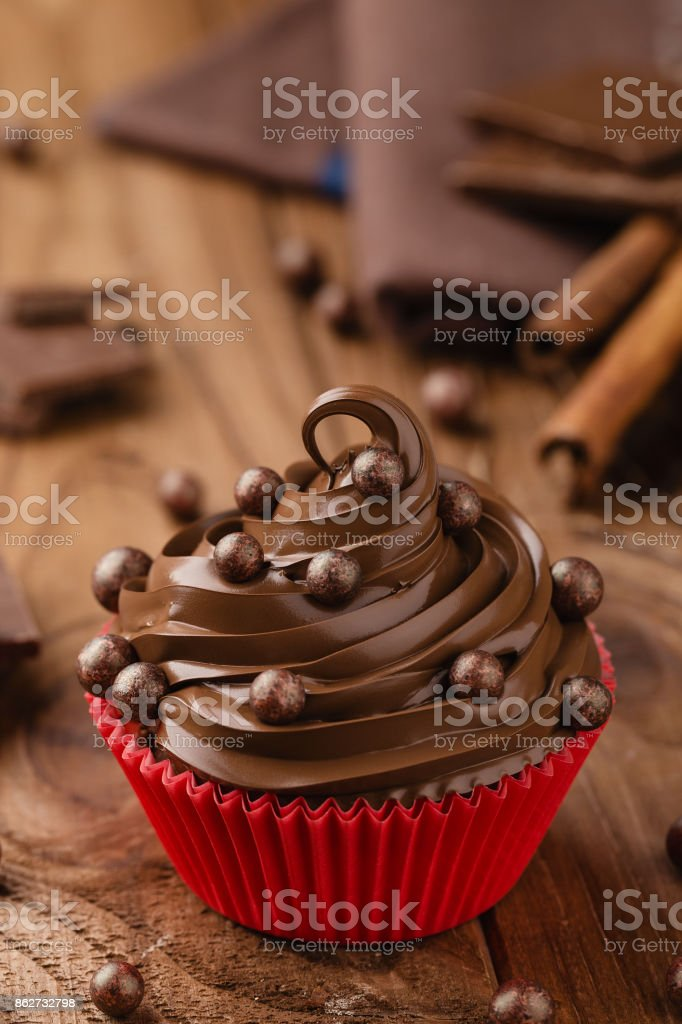 Homemade chocolate cupcake with chocolate chips in red cup stock photo