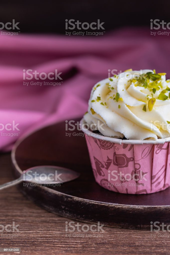 Homemade chocolate muffins or cupcakes with vanilla cream and pistachio on the wooden background stock photo