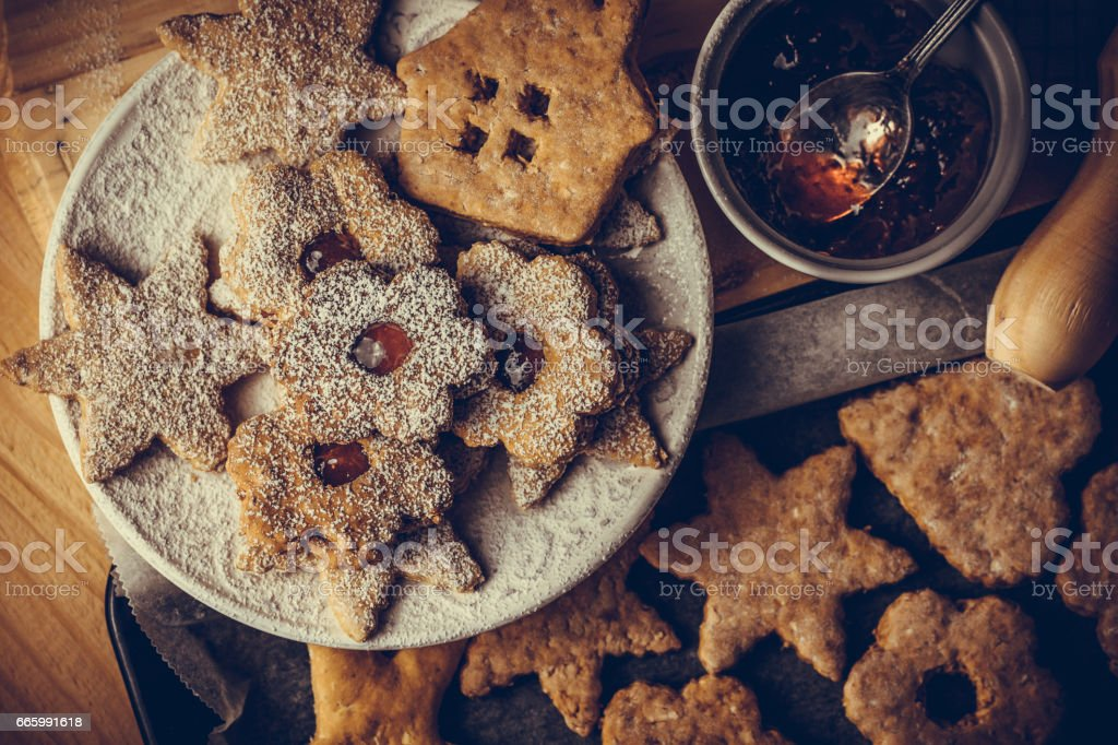 Homemade Christmas gingerbread and linzer cookies with jam, powdered, on baking sheet, top flat view stock photo