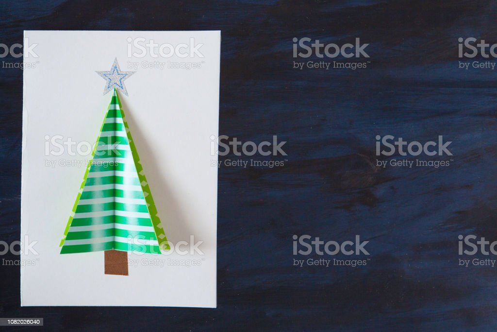 Homemade christmas postcard on dark black background. Green christmas...