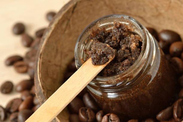 hausgemachter kaffee peeling in einem glas über kokosnussschalen und kaffeebohnen - kaffeepeeling stock-fotos und bilder