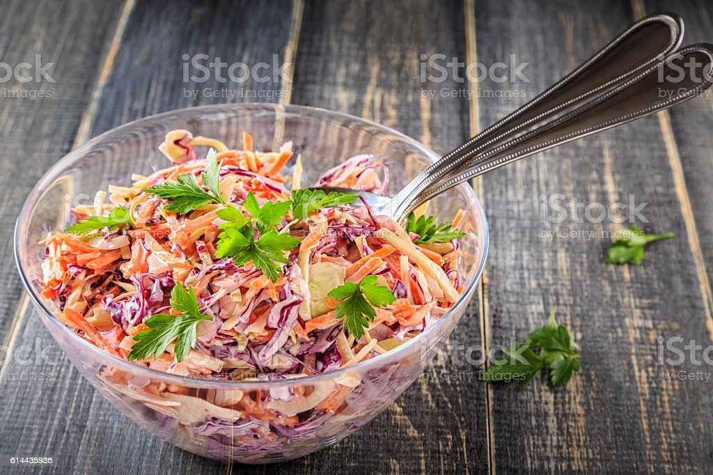 Homemade coleslaw in bowl on dark wooden background. stock photo