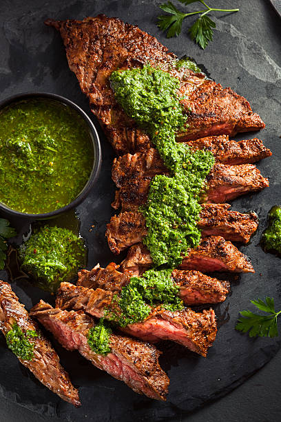 homemade cooked skirt steak with chimichurri - flank steak marinaden stock-fotos und bilder