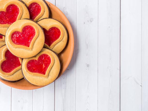 hausgemachte kekse mit einer roten marmelade herz valentinstag weißen hölzernen hintergrund textfreiraum - super torte stock-fotos und bilder