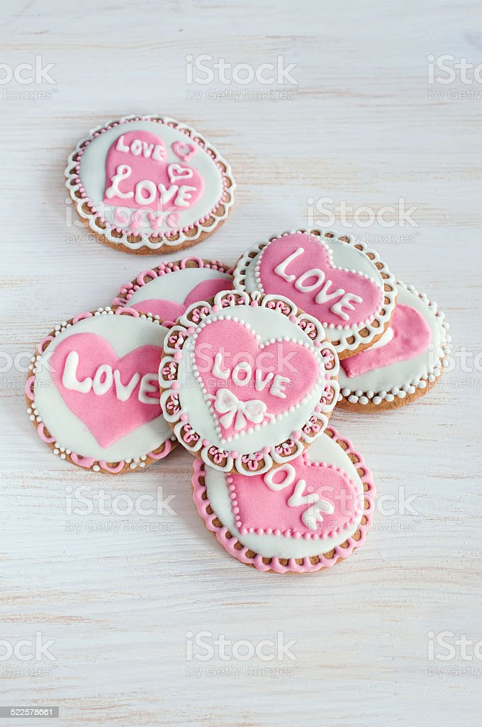 homemade cookies with pink frosting in the shape of hearts stock photo