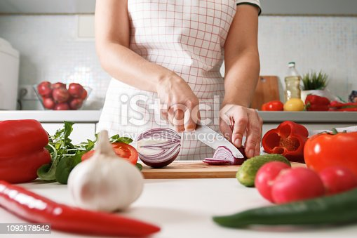 Homemade cooking. Woman in the kitchen cutting red onions on a chopping board. Healthy fresh food.