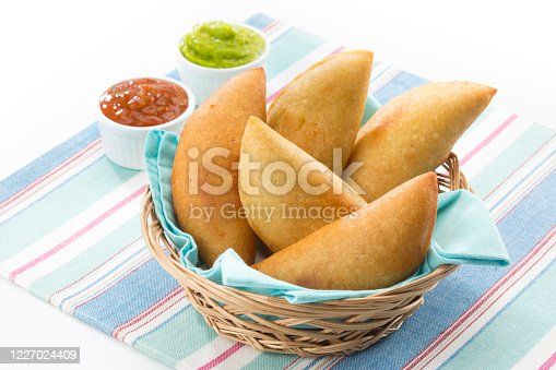 Homemade corn flour empanadas with salsa sauce and guacamole. An empanada is a type of patty baked or fried very popular in many countries of the Americas and in Spain. Empanadas are made by folding dough over a stuffing, which may consist of meat, cheese, fish or other ingredients.