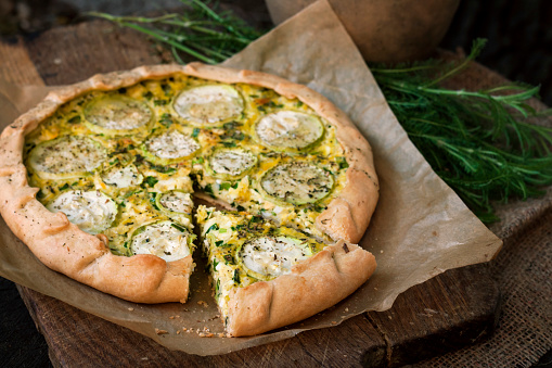 Homemade courgette and goat cheese pie on a dark rustic wooden board background