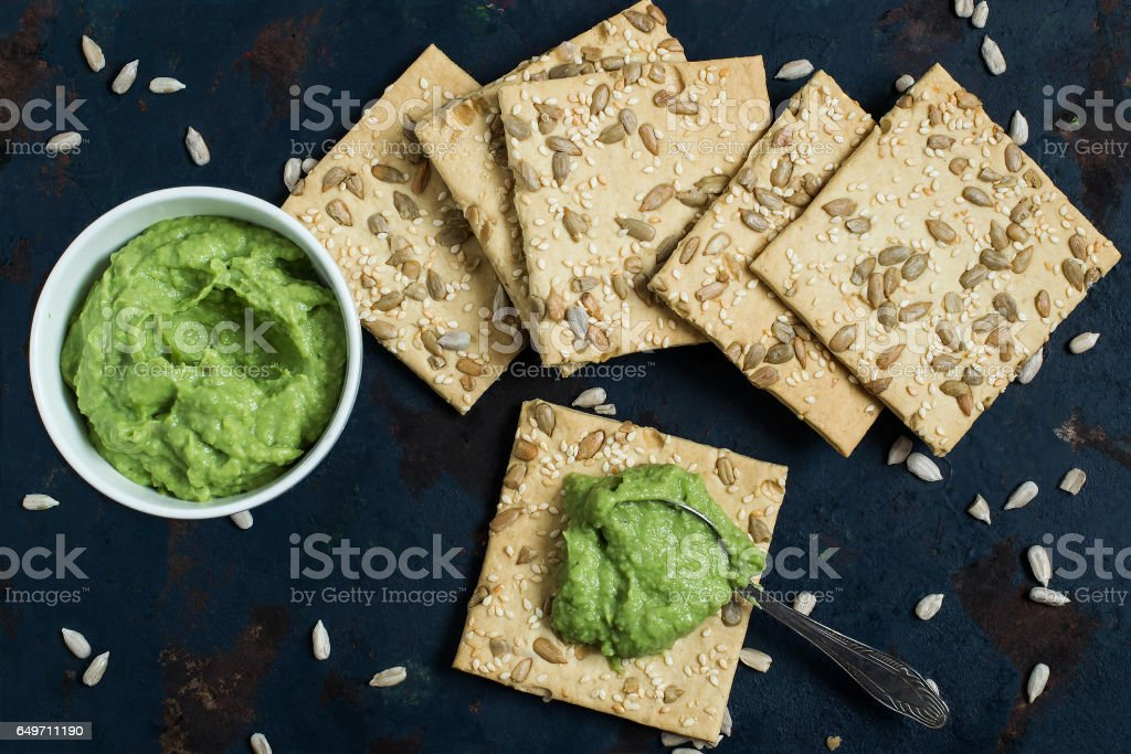 Homemade crackers with sesame, sunflower seeds and guacamole stock photo