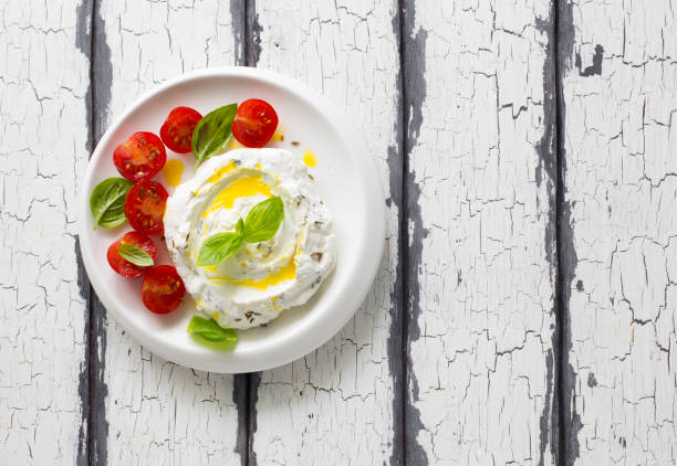 Homemade cream cheese with cherry tomatoes, basil and olive oil stock photo