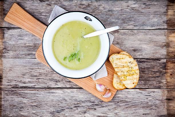 homemade cream soup with asparagus and toasted ciabatta - mergpompoen stockfoto's en -beelden