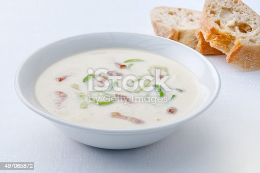 Homemade Creamy Potato and Leek Soup in a white china Bowl, on a white linen tablecloth. Some French bread behind the bowl.