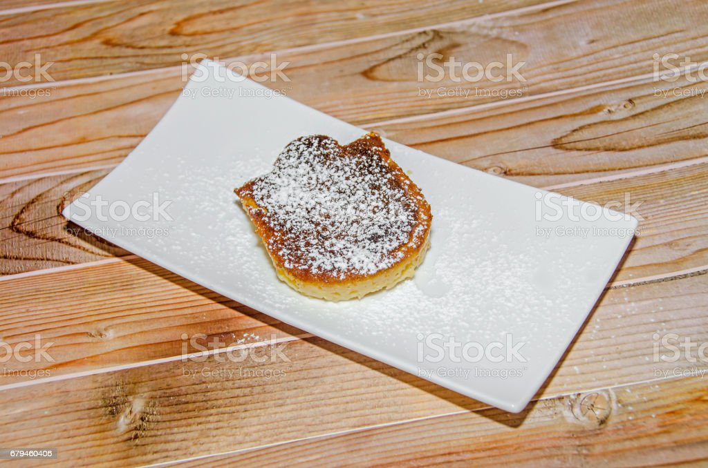 Homemade Creme brulee with powder sugar,  burnt cream, crema catalana, or Trinity cream, white plate and wood background royalty-free stock photo