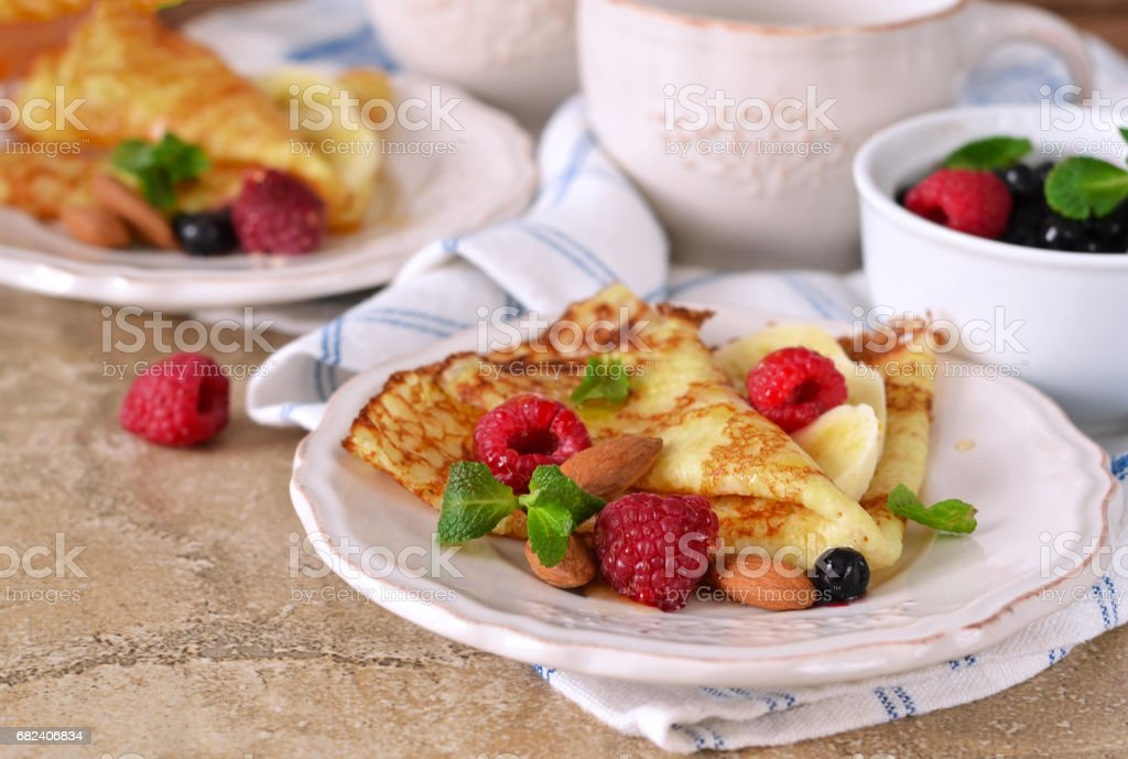 Homemade crepes with maple syrup and berries on a concrete background. royalty-free stock photo
