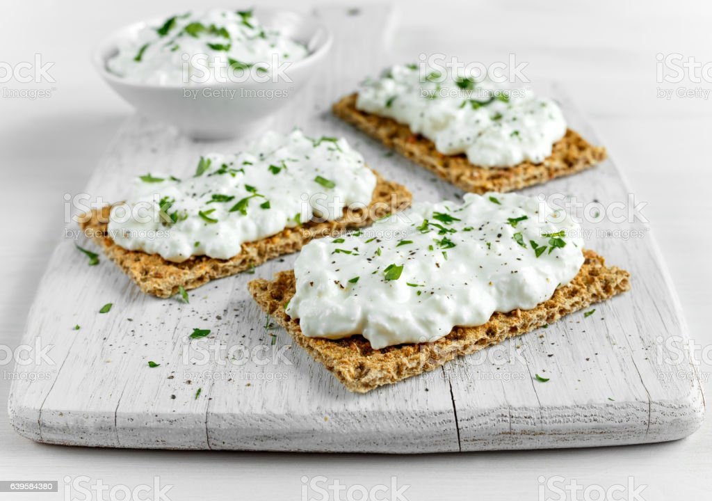 Homemade Crispbread toast with Cottage Cheese and parsley on white stock photo