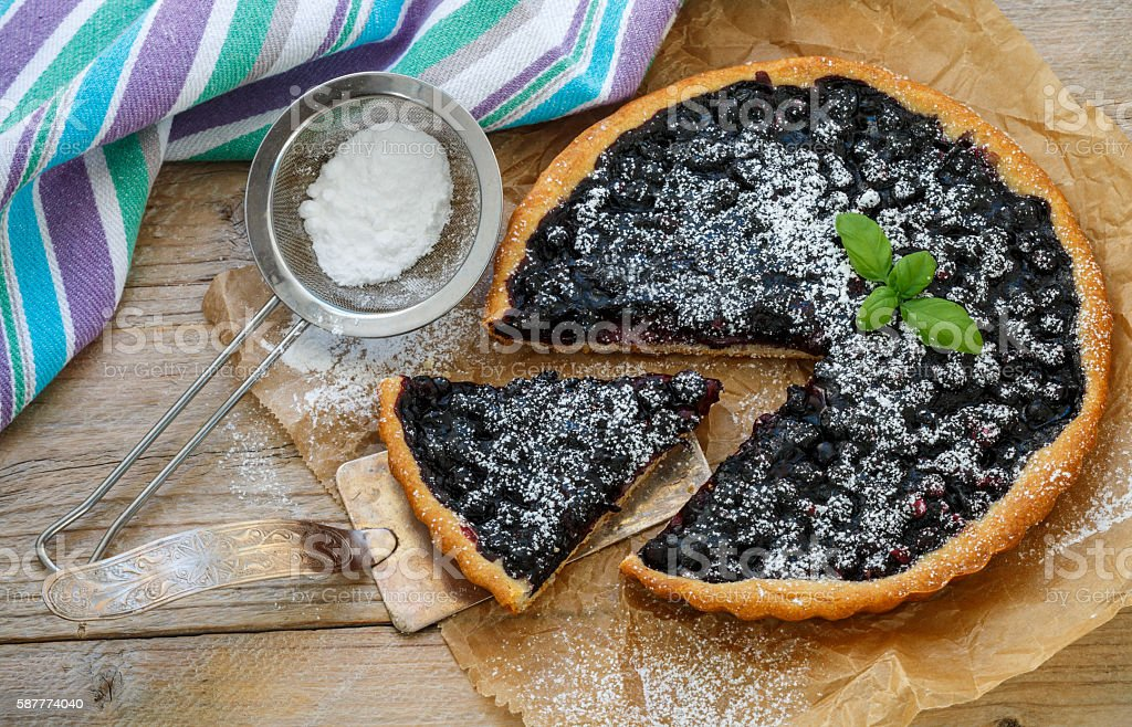 Homemade crispy tart with fresh blueberries and powdered sugar. stock photo