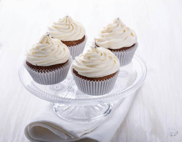 hausgemachte muffins mit frischkäse-glasur - vanille muffins stock-fotos und bilder