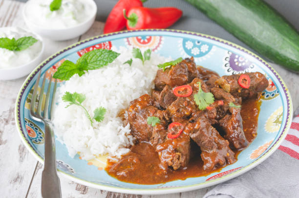 Homemade curry beef stew Homemade beef stew flavored with curry and tomato sauce, served with basmati rice on a plate and tzatziki dip in a Indian cuisine style garam masala stock pictures, royalty-free photos & images