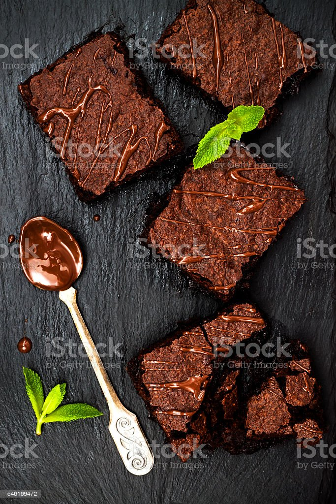 Homemade dark chocolate brownies decorated with strawberries and mint leaves stock photo