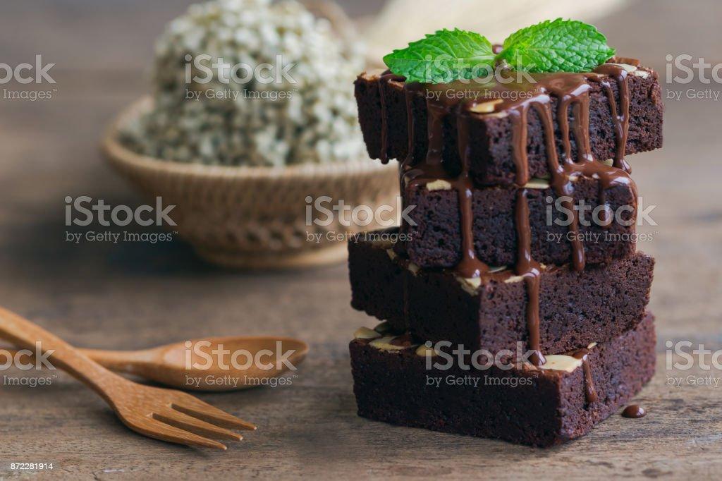 Brownies au chocolat maison sombres garniture avec tranches aux amandes et à la menthe sont empilés sur la table en bois avec espace de copie. Délicieux sucré amer et fudge.