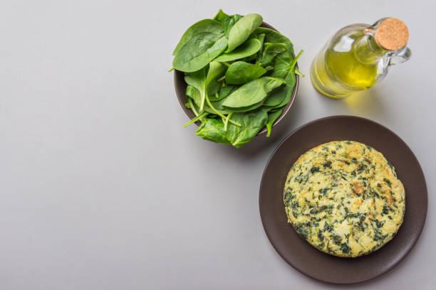 Hausgemachte leckere Kartoffeln Eier Frittata mit Spinat auf Teller. Rezept Zutaten Olivenöl in Flasche auf grauen Küchentisch. Abendessen-Vorbereitung. Über Kopf Draufsicht Textfreiraum – Foto