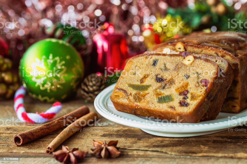 Homemade delicious soft and moist rum fruits cake or Christmas fruits cake with rich dried fruit and nuts slices on wood plate put on wood table with copy for party and celebration. Bakery concept. stock photo
