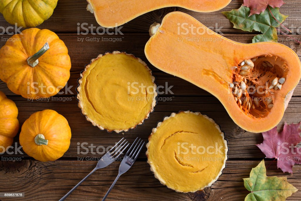 Homemade dessert for Thanksgiving. Open pumpkin pies served with forks, bright orange pumpkins and marple leaves on old wooden background stock photo