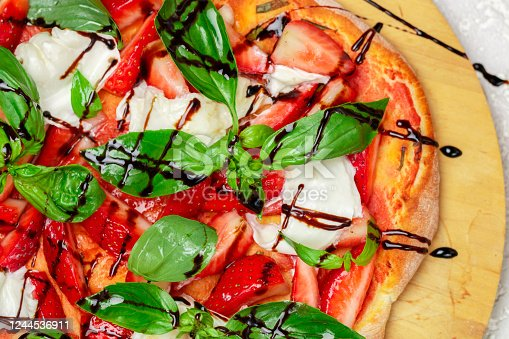 Homemade dessert pizza with tomato sauce, strawberries, burrata cheese, green Basil and balsamic close-up. Top view, selective focus
