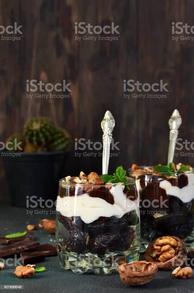 A homemade dessert with vanilla cream, cookies, prunes and nuts. stock photo