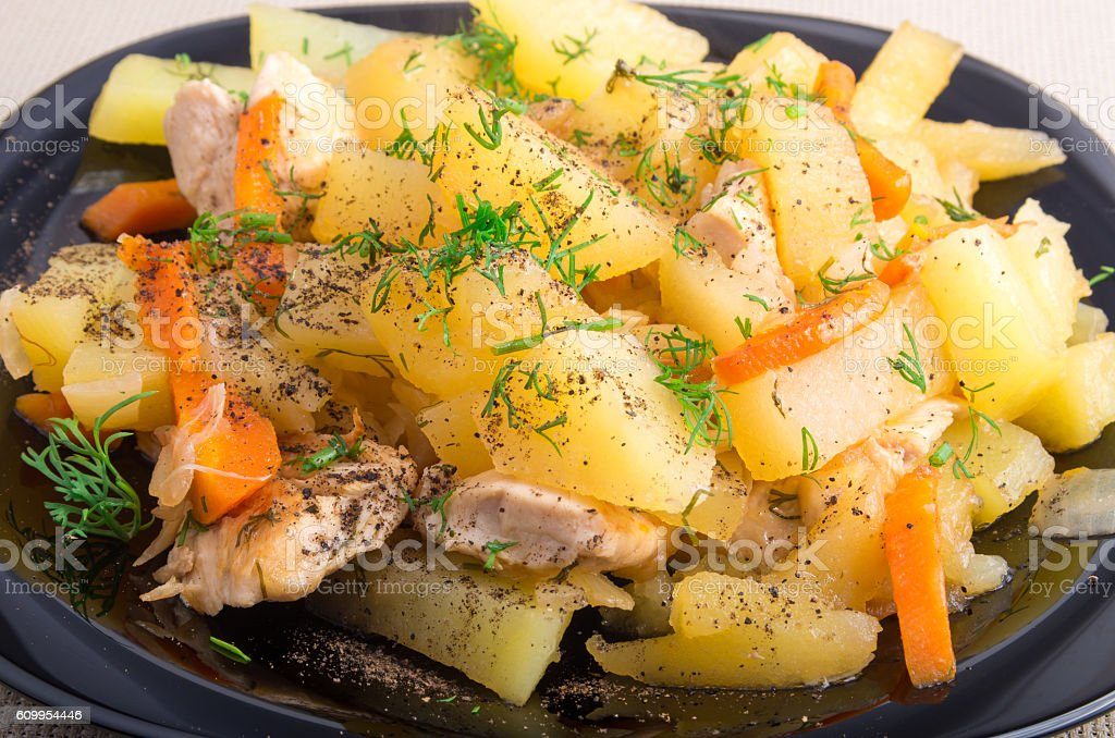 Homemade dish of slices of stewed potatoes, chicken, carrot and stock photo