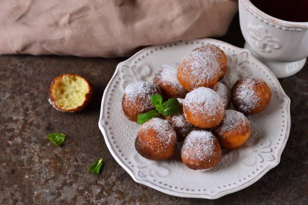 selbstgemachte donuts mit puderzucker zum frühstück auf dem alten grunge hintergrund - hausgemachte gebackene donuts stock-fotos und bilder