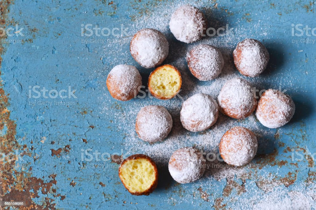 Homemade donuts with powdered sugar on a blue, old background stock photo