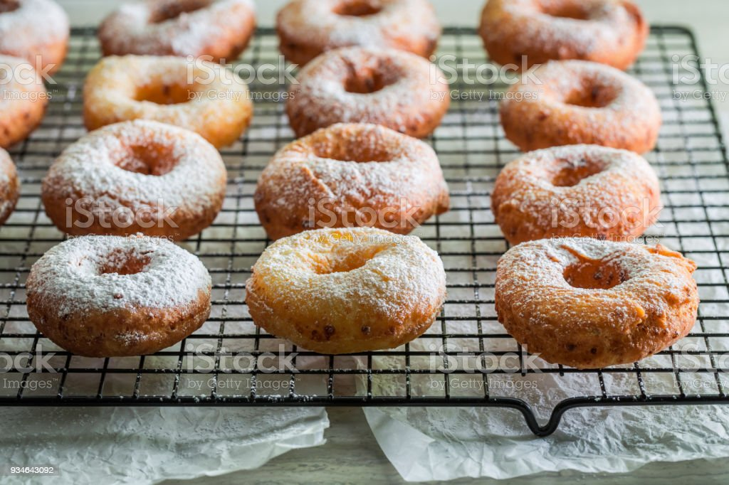 Homemade donuts with powdered sugar on metal grate stock photo