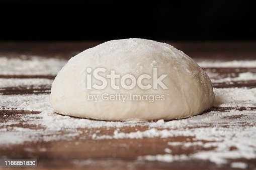 Homemade yeast dough ball for pizza on floured wooden table